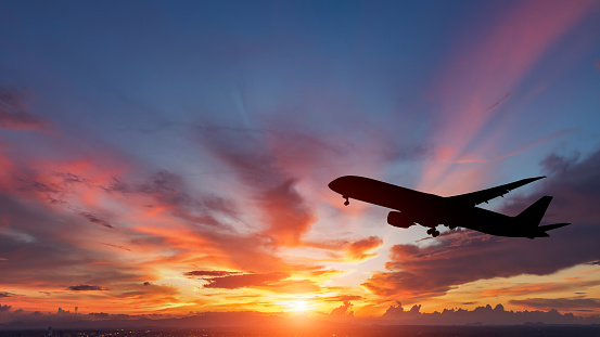The silhouette of a passenger plane flying in sunset.