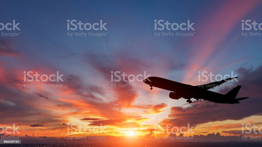La silhouette d'un avion de passagers volant au coucher du soleil. - Photo