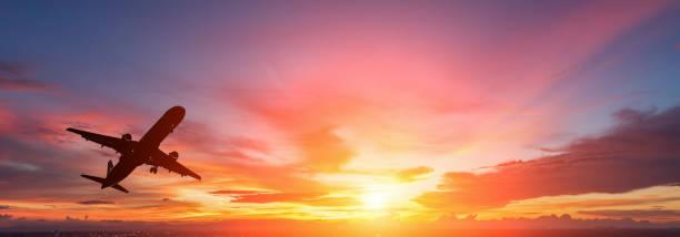 Die Silhouette eines Passagier-Flugzeug fliegen im Sonnenuntergang. – Foto