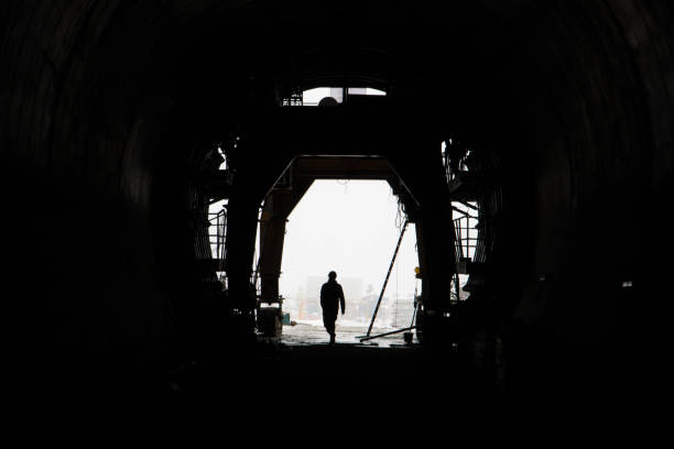 The silhouette of a person in a high-speed railway tunnel under construction. stock photo