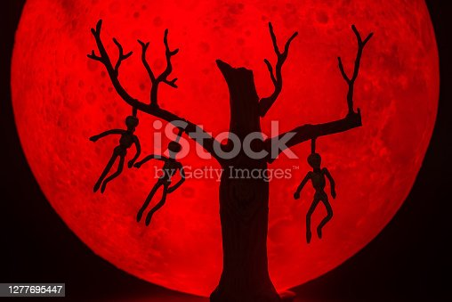 The silhouette of a tree standing dead with a man hanged dead to the bone. There's a red full moon in the background. Halloween horror concept.