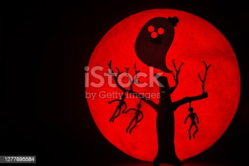 The silhouette of a tree standing dead with a man hanged dead to the bone and Ghost spirit. There's a red full moon in the background. Halloween horror concept.