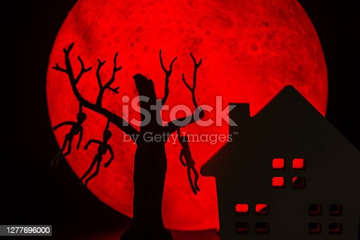 The silhouette of a tree standing dead with a man hanged dead to the bone and Horror haunted house. There's a red full moon in the background. Halloween horror concept.