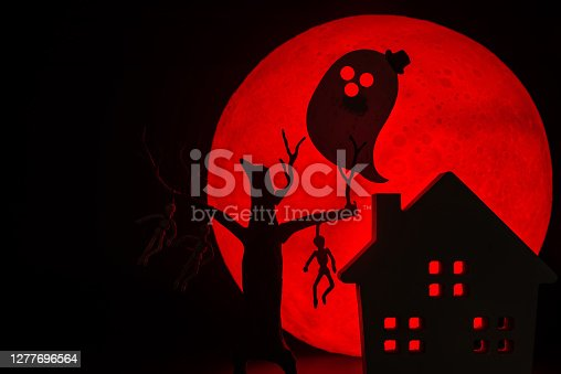 The silhouette of a tree standing dead with a man hanged dead to the bone, Ghost spirit and Horror haunted house.There's a red full moon in the background. Halloween horror concept.