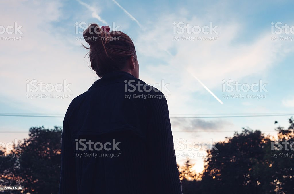The silhouette of a young woman looking at sunset stock photo