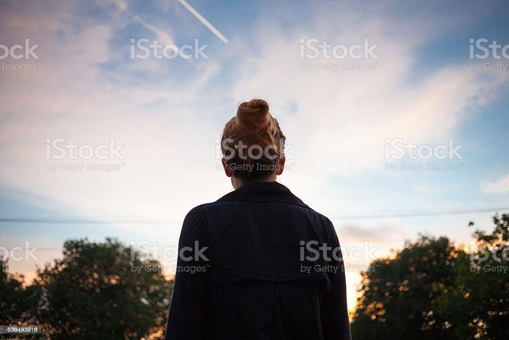 Die silhouette von eine junge Frau schaut an Sonnenuntergang – Foto