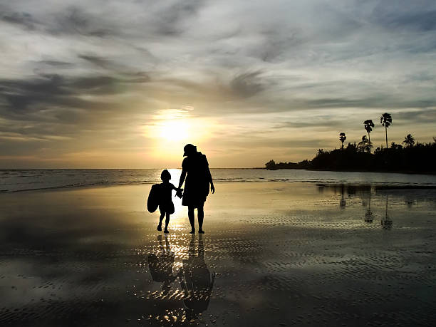The silhouette of family watching the sunrise on the beach stock photo