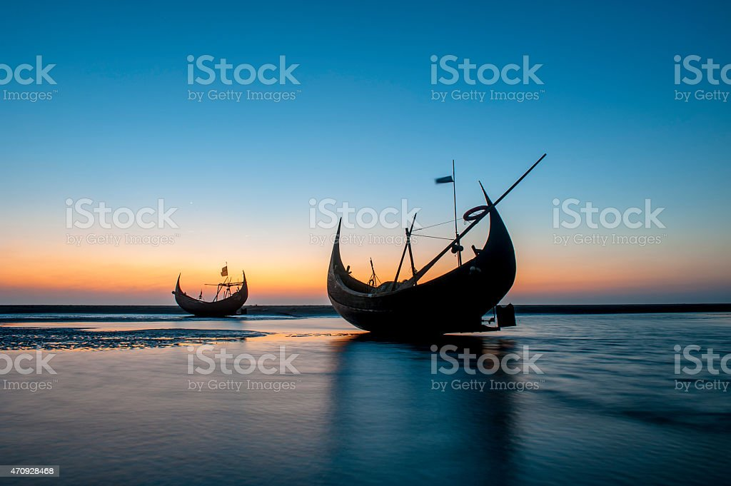 The silhouette of fishing boat on beach, Bangladesh stock photo