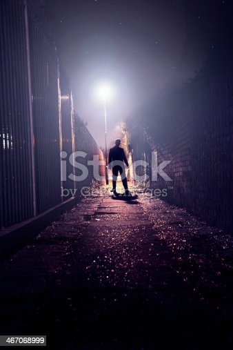 The silhouette of a suited man standing aggressively in a dark alley.