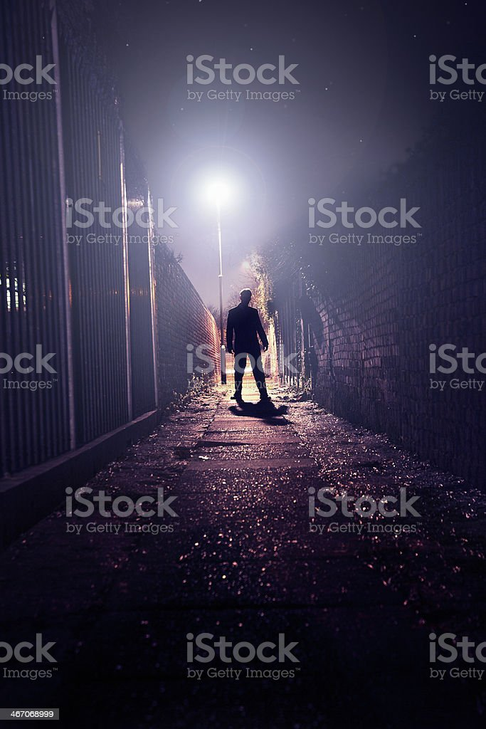 The silhouette of man standing in dark alley. stock photo