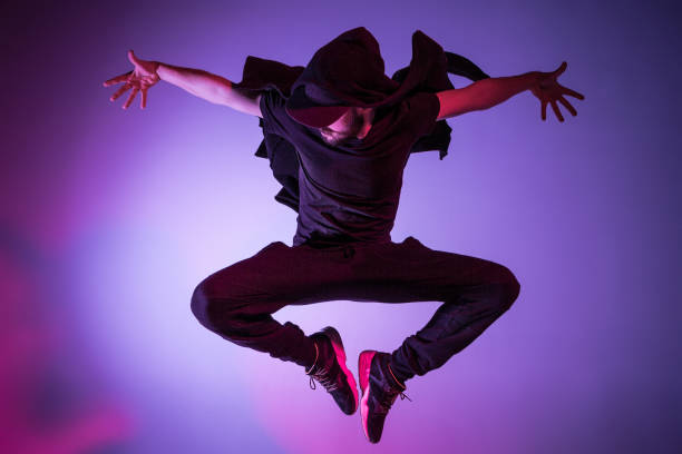 the silhouette of one hip hop male break dancer dancing on colorful background - dance music stock pictures, royalty-free photos & images