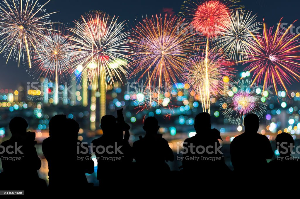 The silhouette of reporter photograph the Fantastic festive new years colorful fireworks on cityscape blurred photo bokeh,project success, holiday concept stock photo