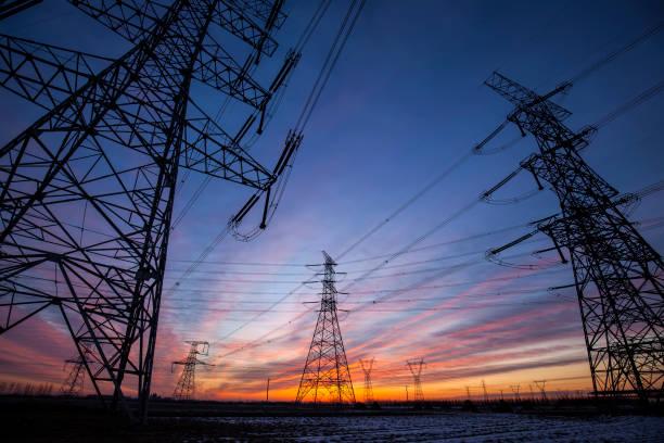 the silhouette of the evening electricity transmission pylon - elettricità foto e immagini stock