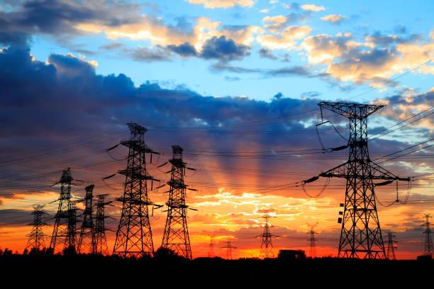 La silueta de la noche de transmisión torre de conducción eléctrica - foto de stock