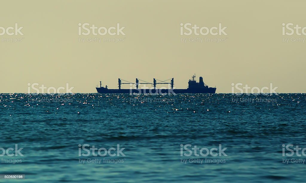 The silhouette of the ship on the sea stock photo