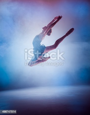istock The silhouette of young ballet dancer jumping on a blue 498747514
