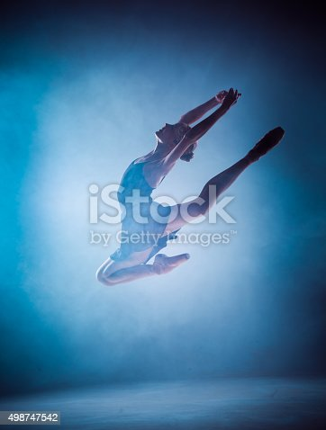 476021886 istock photo The silhouette of young ballet dancer jumping on a blue 498747542