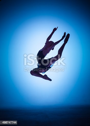 476021886 istock photo The silhouette of young ballet dancer jumping on a blue 498747744