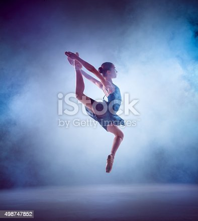 476021886 istock photo The silhouette of young ballet dancer jumping on a blue 498747852