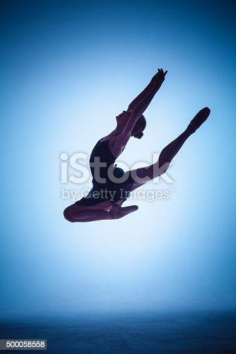 476021886 istock photo The silhouette of young ballet dancer jumping on a blue 500058558