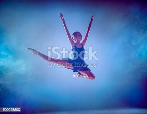 476021886 istock photo The silhouette of young ballet dancer jumping on a blue 500058800