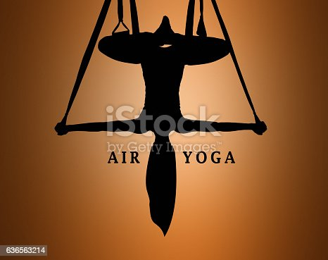 istock The silhouette of Young woman doing anti-gravity aerial yoga 636563214