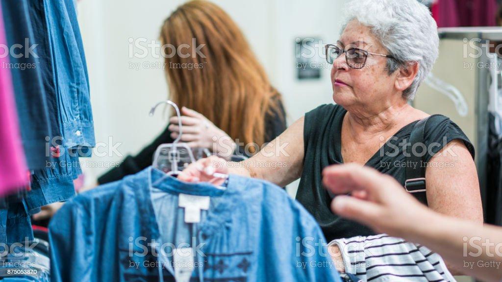 La femme senior active argentée de 65 ans et son granddaughther adolescent, faire du shopping dans le magasin de vente au détail de vêtements - Photo