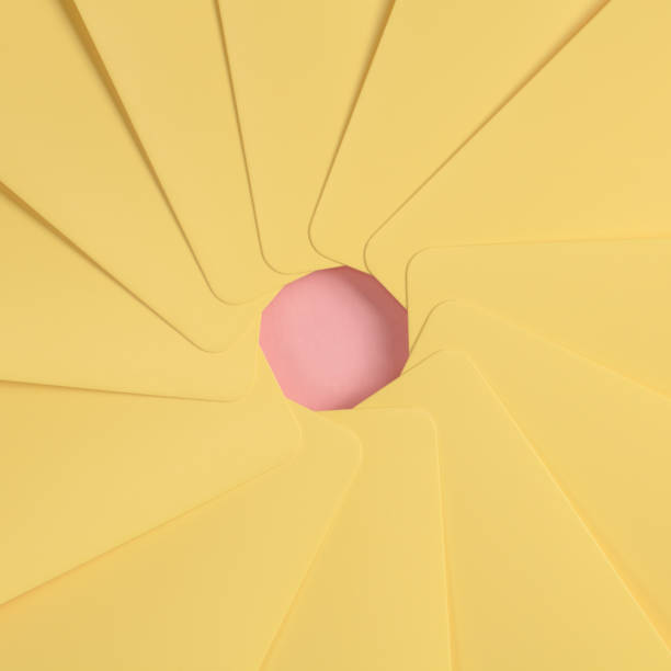 The simbol of an aperture of a camera is made from yellow paper on the pink background. stock photo