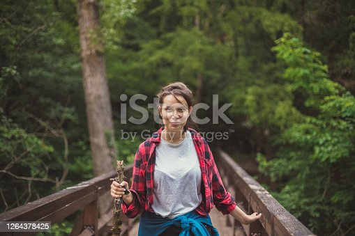 Centered view of a woman walking over a wooden bridge dividing the park and wild woods she just got out of. By the look on her face, it seems like she enjoyed the hike.