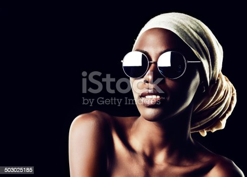 Studio shot of a beautiful woman wearing a headscarf against a black background