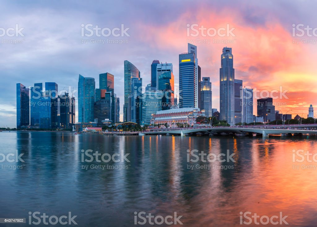 The Singapore Downtown and Marina Bay Business District Skyline at twilight with sunset illuminating the clouds and sky stock photo