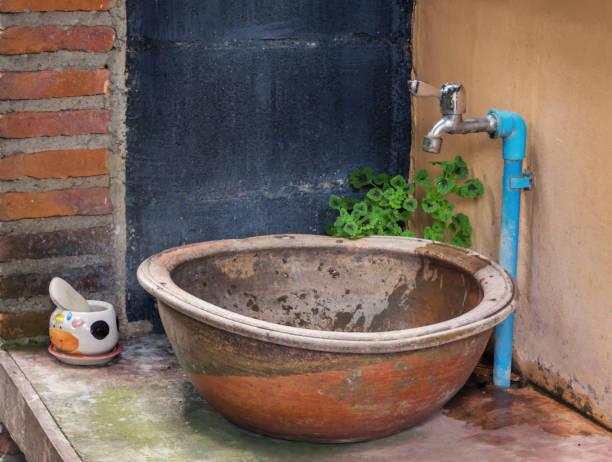die waschbecken haben ein retro-design mit der topfpflanze sinkt entsprechend der orange betonwände zu versinken. - badezimmer new york style stock-fotos und bilder
