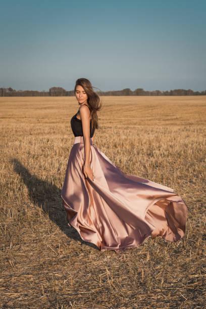 der rock bläst der wind. mädchen außerhalb der stadt im herbst feld - damen rock pink stock-fotos und bilder