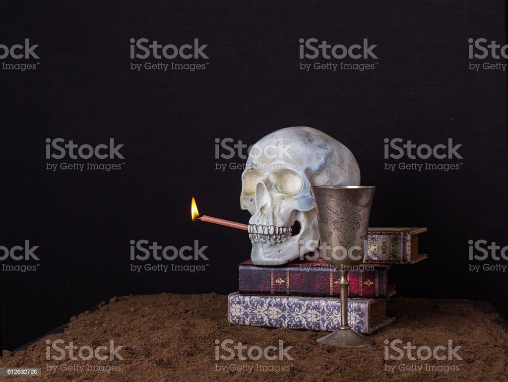 The skull is holding in his mouth a burning candle stock photo