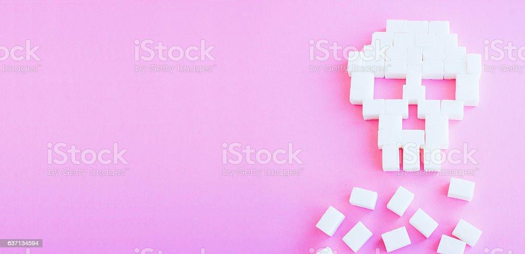 The skull made of sugar cubes. Sugar kills. Pink background stock photo