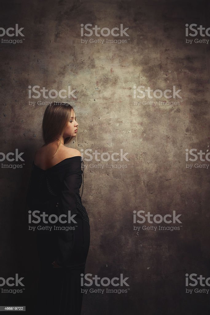 The slender girl stands near  beautiful wall stock photo