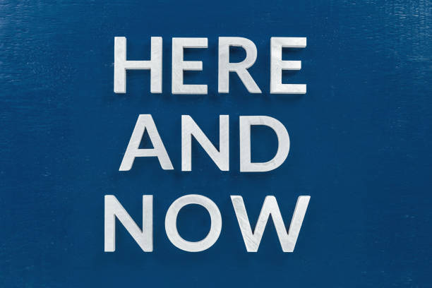 the slogan here and now laid with silver metal letters on classic blue painted board background stock photo