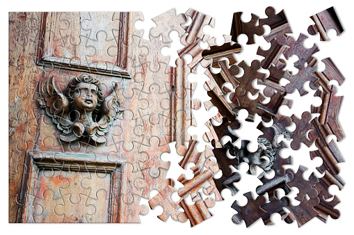 istock The slow construction of faith - concept image with a sculpture of an angel on a wooden door - concept image in jigsaw puzzle shape 1154959577