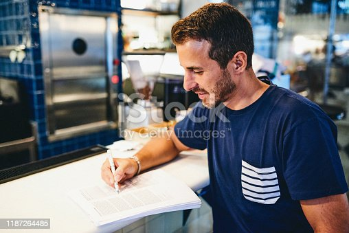 Shot of a man going through paperwork while working in a bar