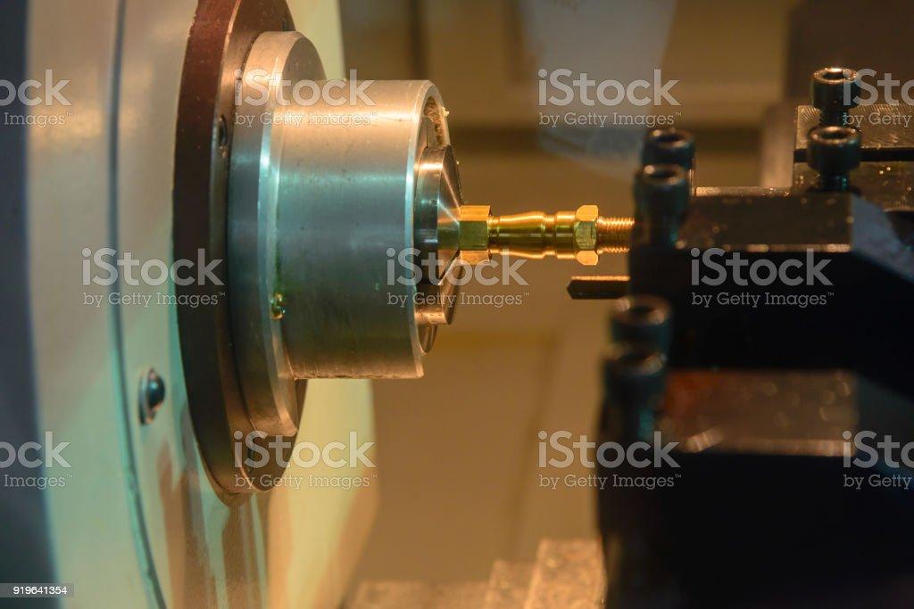 The small CNC lathe cutting the brass shaft stock photo
