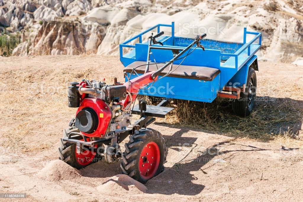 The small handy farm machine motor plow with cart closeup standing in...