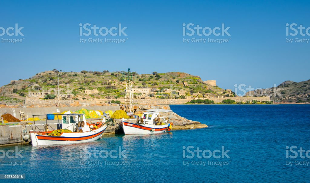 The small harbor of Plaka with traditional fishing boats, sailing rope on the dock, and the island of Spinalonga at the background, Crete, Greece. stock photo