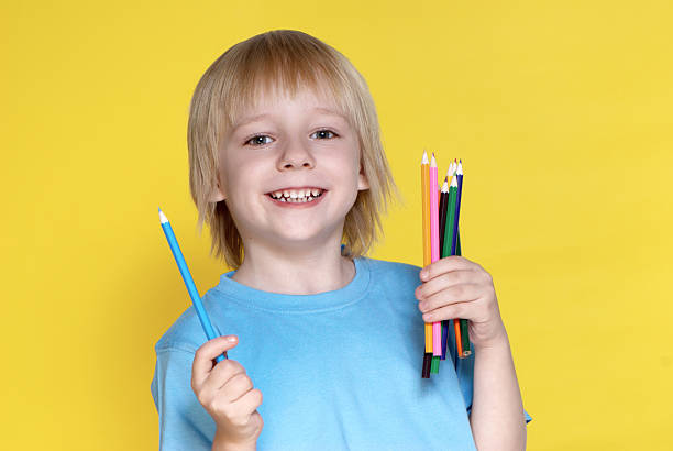 The small schoolboy with pencils on a yellow background stock photo