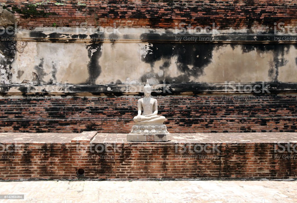 The small white Statue Buddha and brick wall. stock photo