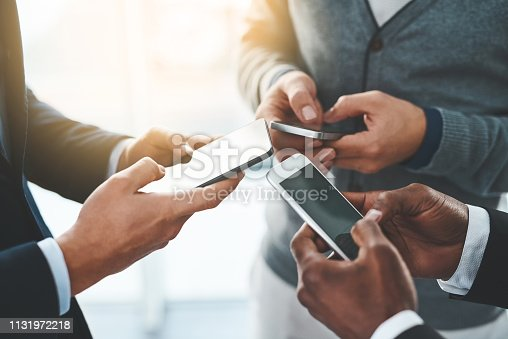 High angle shot of a group of unrecognizable businesspeople using their cellphones in the office
