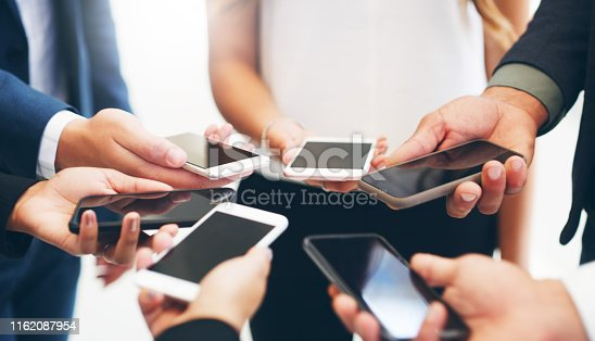 Cropped shot of a group of businesspeople standing in a circle and using their smartphones in a modern office