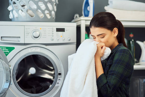 The smell of fresh laundry Cropped shot of an attractive young woman smelling a freshly washed towel while doing laundry at home laundry detergent stock pictures, royalty-free photos & images