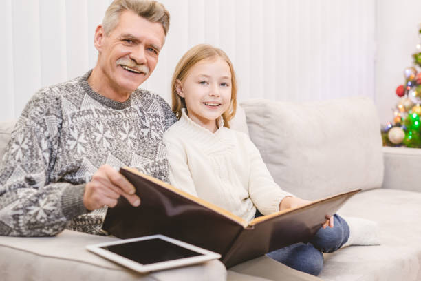 the smile girl with a grandfather read the book near the christmas tree - holiday and invoice family foto e immagini stock