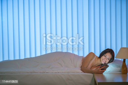 istock The smile woman lay on the bed and phone. Evening night time 1144410520