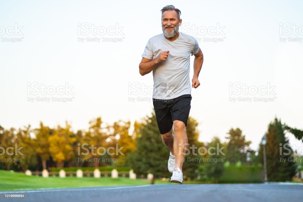 The smiling happy elderly man running on the road